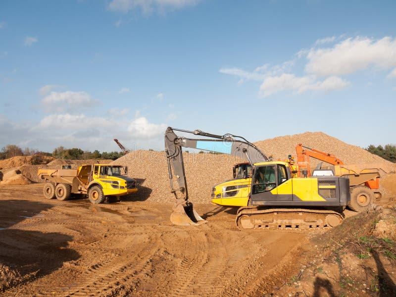 Två parkerad lastbil och grävare för branschkonstruktionsvillebråd arkivbild