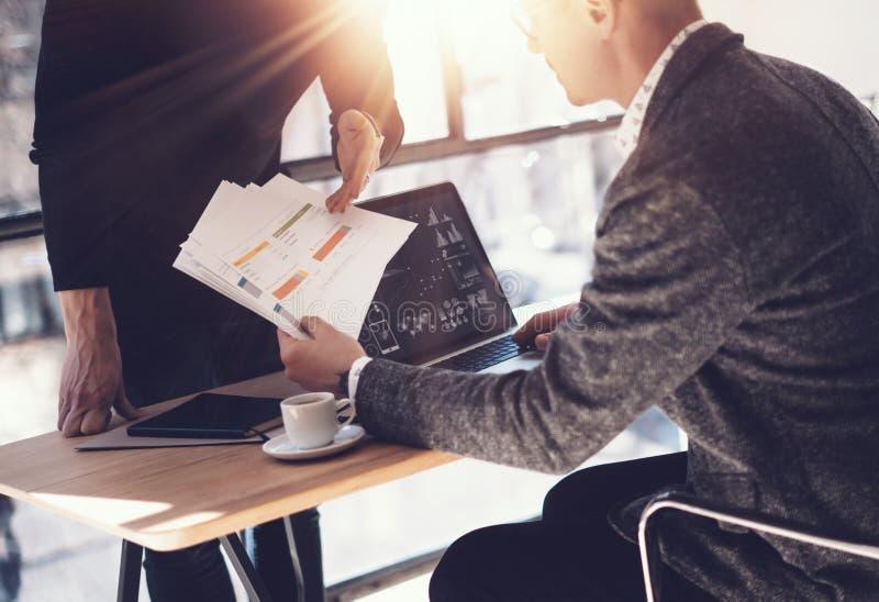 Två partners som gör forskning för ny affärsriktning Vuxen affärsman som arbetar den moderna bärbara datorn och visar dokument ti arkivfoto