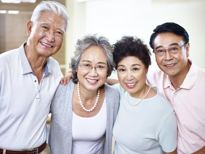 Två pensionärasiatpar som tillsammans får arkivfoton