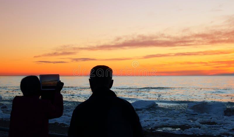 Två pensionärer som använder teknologi för att fånga ursnygg vårsolnedgång över Lake Huron royaltyfri fotografi