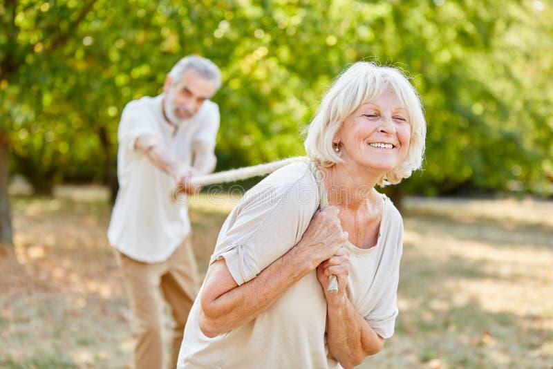 Två pensionärer som spelar dragkampen royaltyfria bilder