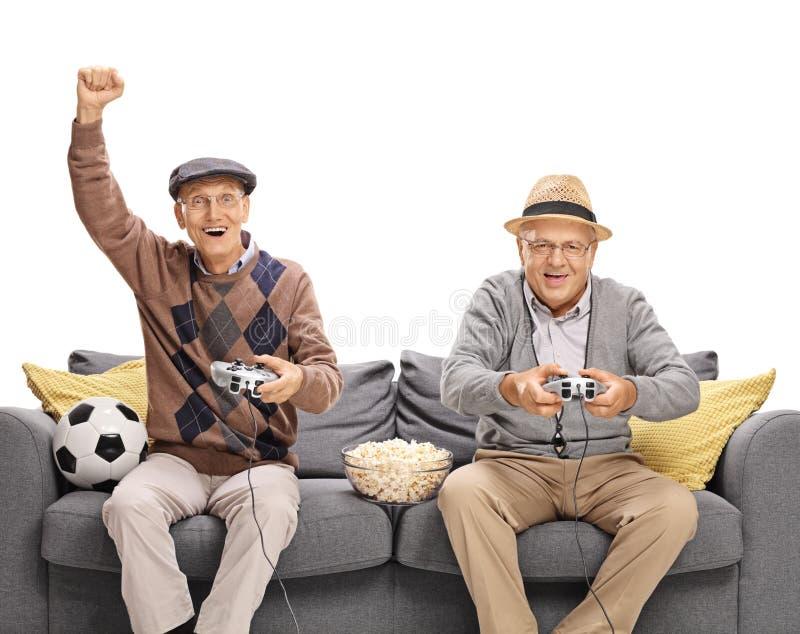 Två pensionärer som spelar fotbollvideospelet fotografering för bildbyråer