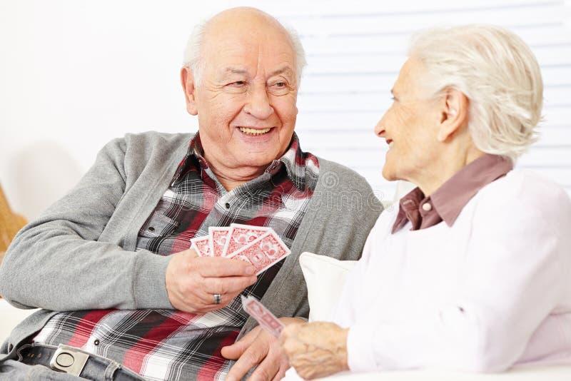 Två pensionärer som spelar kort royaltyfria bilder