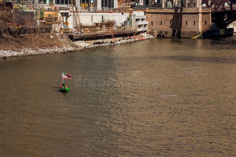 Två personer i en dag för St Patricks dekorerade kanoten med amerikanska flaggan, som de förbigår en konstruktionsplats på Chicag royaltyfri bild