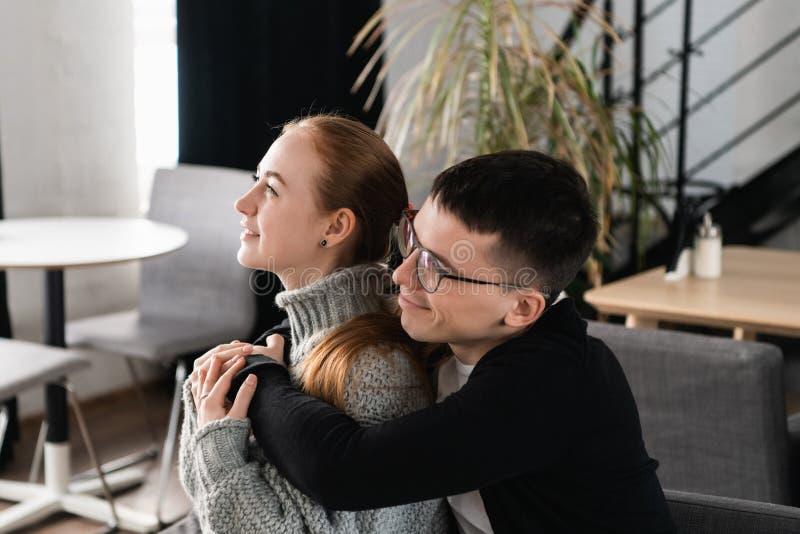 Två personer, man och kvinna i kafé som kramar, skrattar och tycker om tidutgifter med de Koppla ihop förälskat på a royaltyfri fotografi