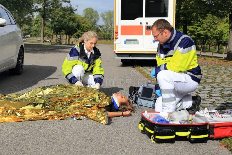 Två personer med paramedicinsk utbildning som hjälper en kvinna efter en trafikolycka med den guld- filten arkivfoton