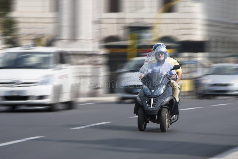 Två personer på en sparkcykelbeverly tre-hjul sparkcykel (som panorerar effekt) royaltyfri bild