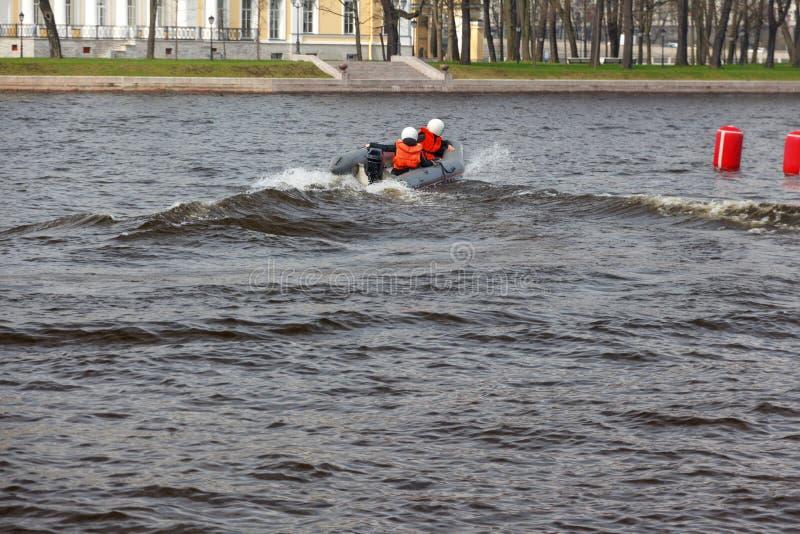 Två personer rider ett uppblåsbart fartyg med en motor wate för barn` s fotografering för bildbyråer