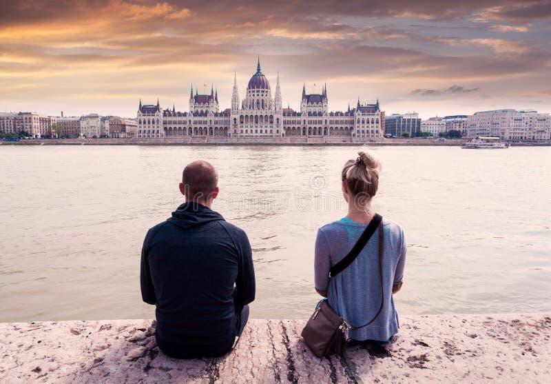 Två personer sitter på stranden och tycker om sikten av parlamentet i Budapest, Ungern royaltyfri foto