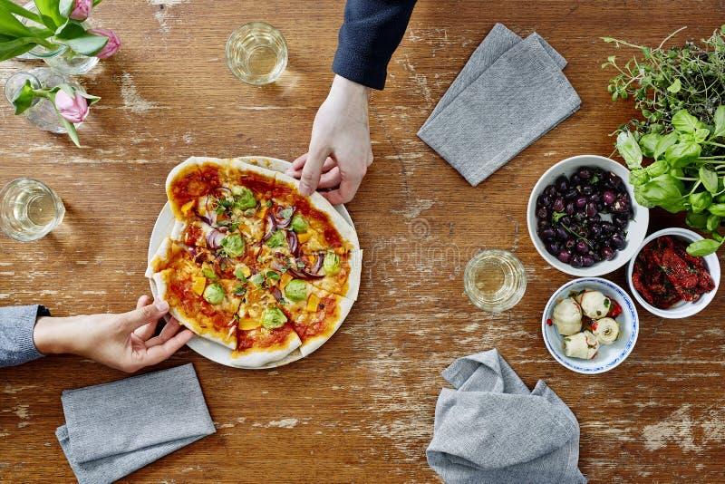 Två personer som delar nytt gjord vegetarisk pizza royaltyfria bilder