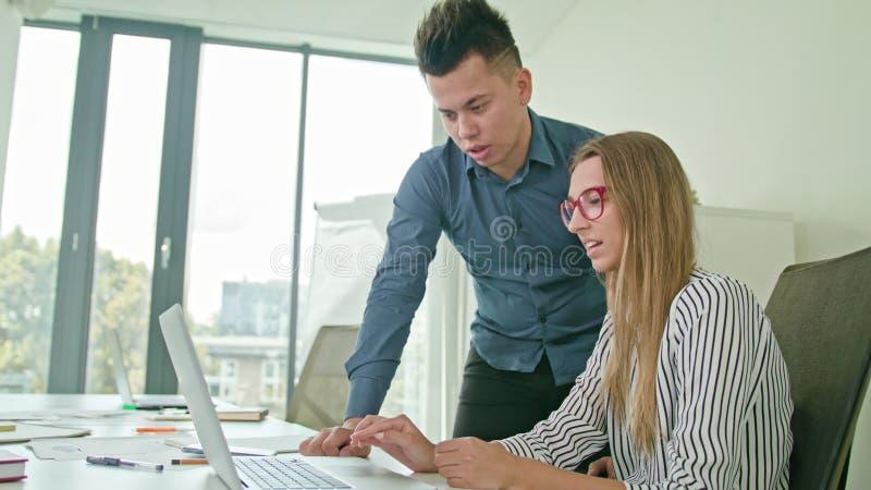 Två personer som diskuterar idéer genom att använda bärbara datorn royaltyfria foton