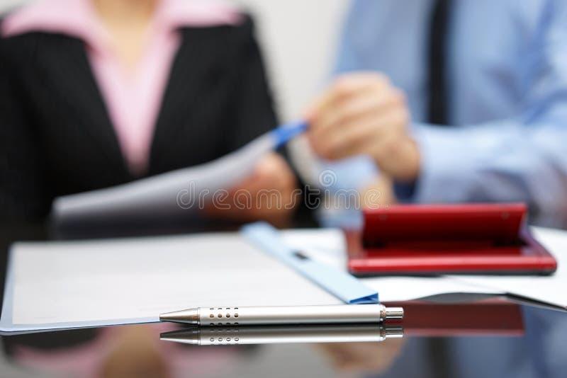 Två personer som diskuterar om rapport på affärsmöte med focu royaltyfri bild