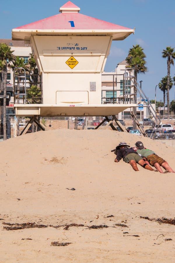 Två personer som framme lägger på sanden, i solen av en livräddareställning med deras hattar över deras framsidor royaltyfria bilder