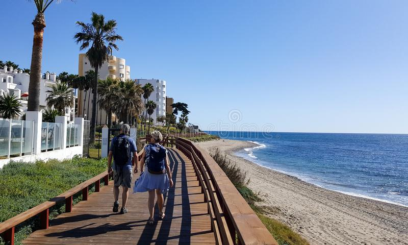 Två personer som går på kusten av medelhavs- arkivbild