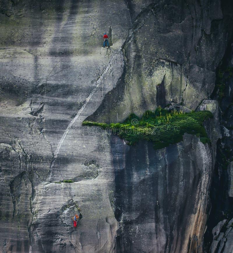 Två personer som klättrar en vägg med en grön fläck fotografering för bildbyråer