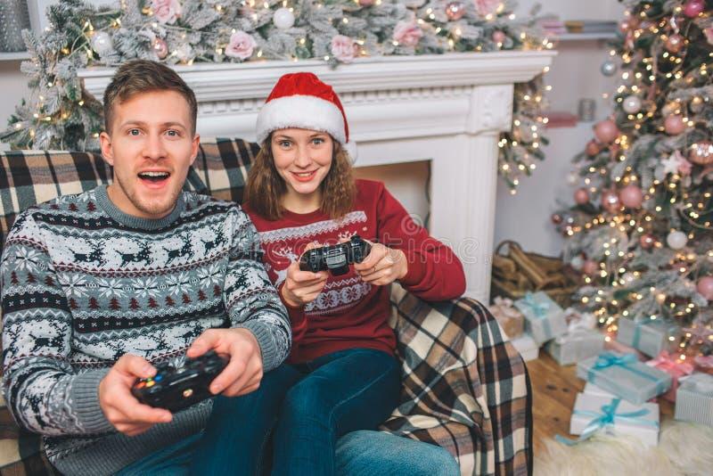 Två personer som sitter och spelar lekar De rymmer gamepads i händer Den unga mannen och kvinnan upphetsas Dem tryckknappar arkivfoton