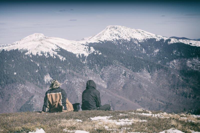 Två personer som sitter på en kulle arkivbilder