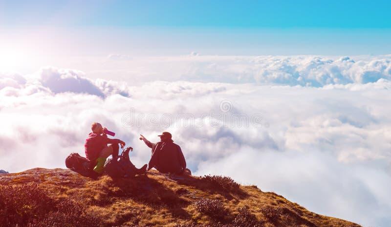 Två personer som sitter på ovannämnda moln för hög klippa i berg arkivbild