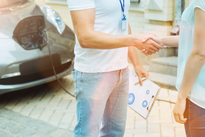 Två personer som skakar händer, medan stå nära bilen fotografering för bildbyråer