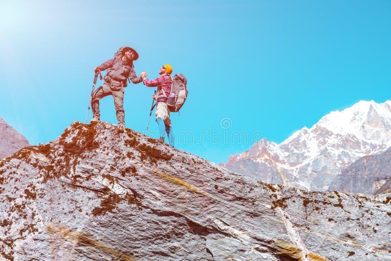Två personer som skakar händer på bergtoppmöte arkivbilder