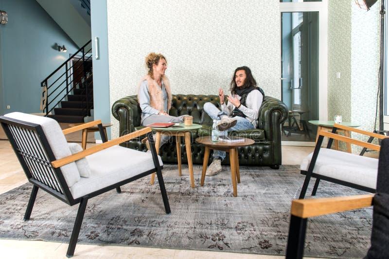 Två personer som talar i en vardagsrum royaltyfri fotografi