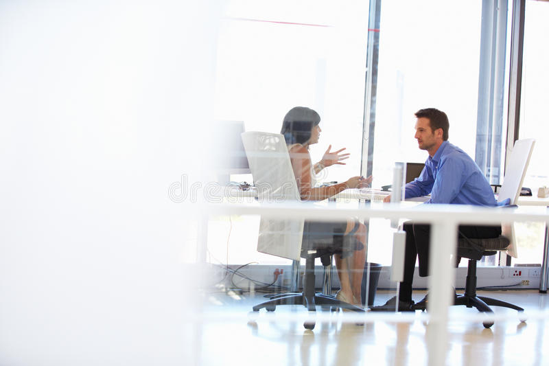 Två personer som talar i ett kontor royaltyfria bilder