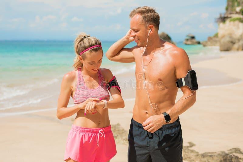 Två personer som tillsammans utbildar på stranden royaltyfri bild
