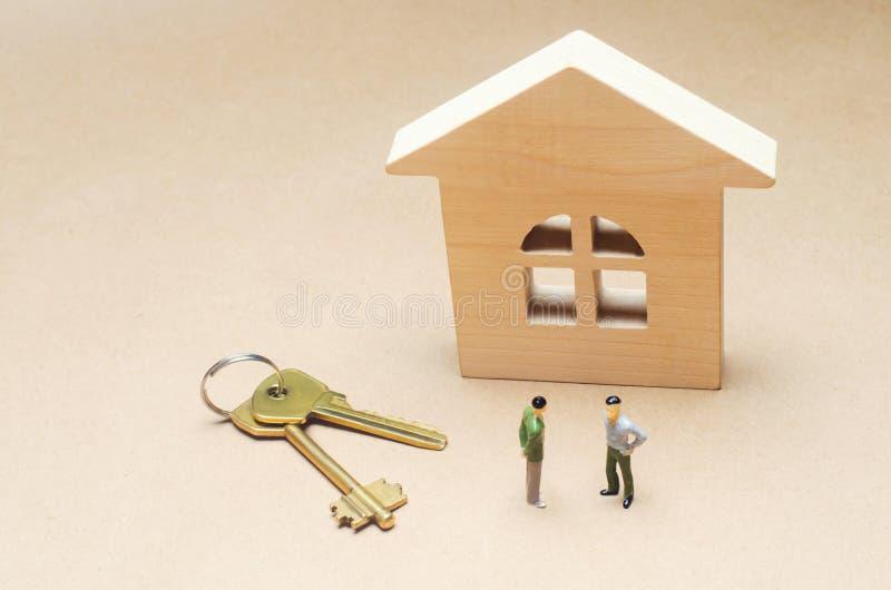 Två personer står nära ett trähus verkligt begreppsgods köpa och sälja en lägenhet hyra för hus avtalssi arkivfoto