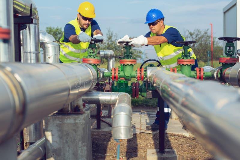 Två petrokemiska arbetare som kontrollerar tryckventiler på en bränslebehållare royaltyfria foton