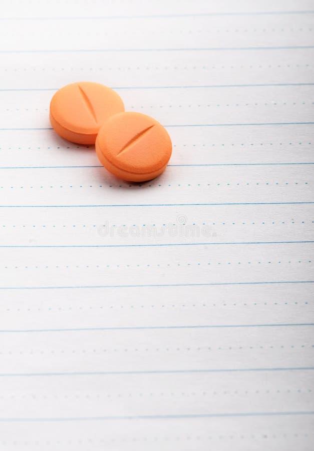 Två pills på fodrat papper fotografering för bildbyråer