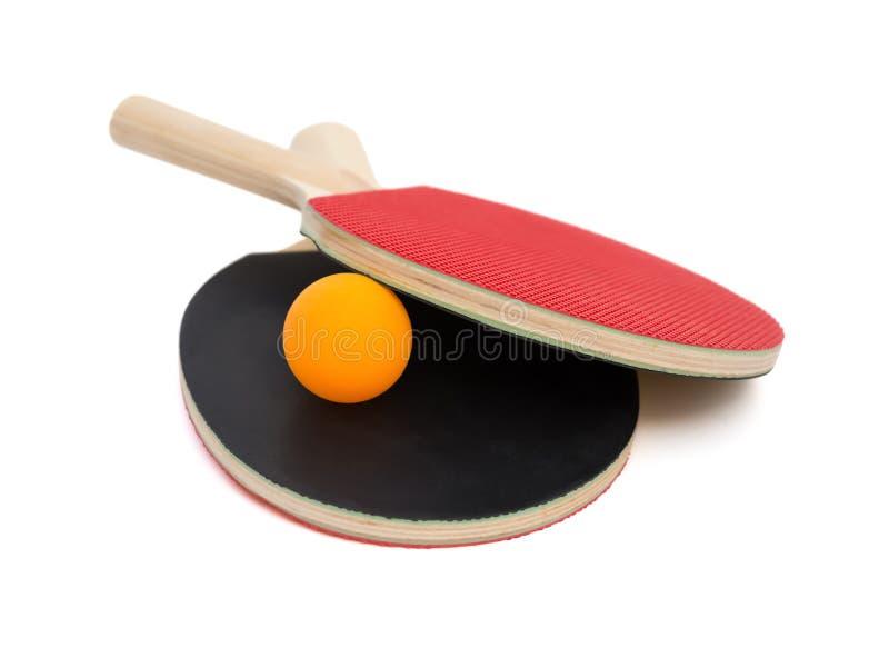 Två pingpongracket och en boll med den snabba banan royaltyfria foton