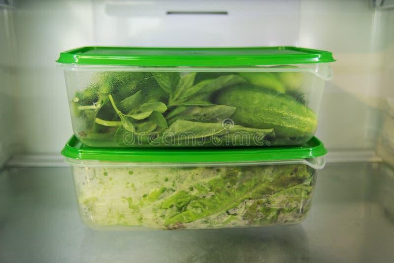 Två plast- matbehållare med den gröna grönsaken på en hylla av en kyl arkivbild