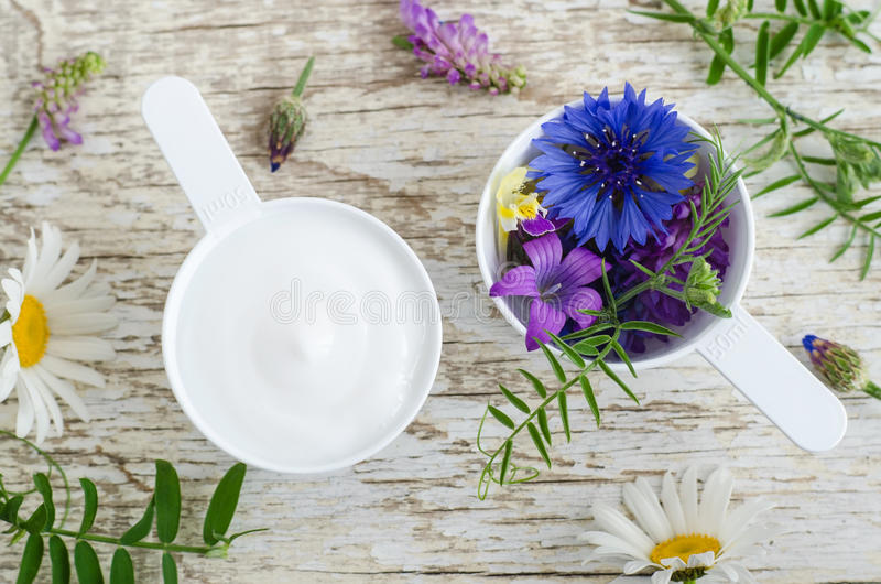 Två plast- skopor med olika lösa blommor och ansiktsbehandlingkrämmaskering med växt- extrakter Ingredienser av den naturliga skö royaltyfria foton