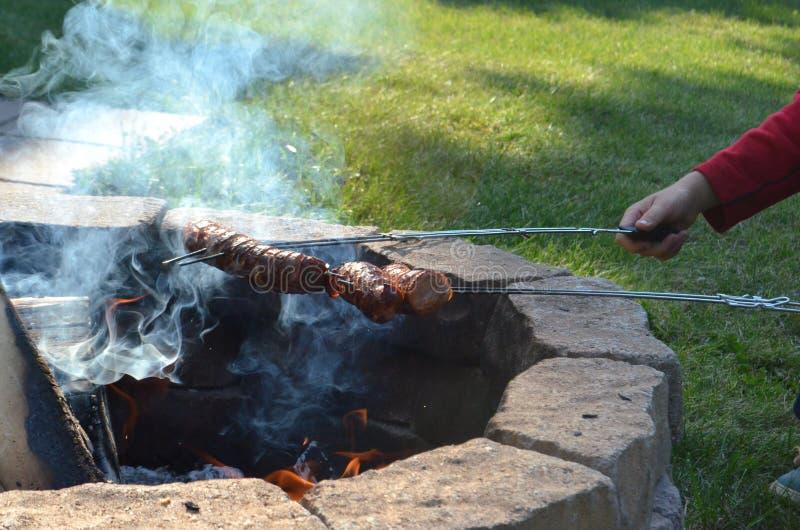 Två pojkar är grilla eller grilla polska korvar över en öppen brandgrop i deras trädgård royaltyfri foto