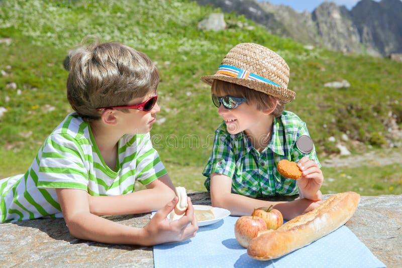 Två pojkar äter ost och bröd i berg arkivfoto