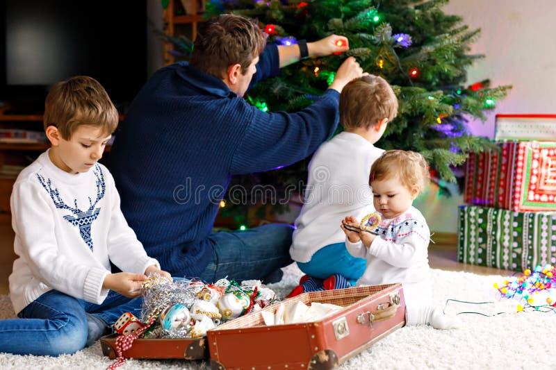 Två pojkar för liten unge och förtjusande behandla som ett barn flickan som dekorerar julgranen med gamla tappningleksaker och bo royaltyfri fotografi