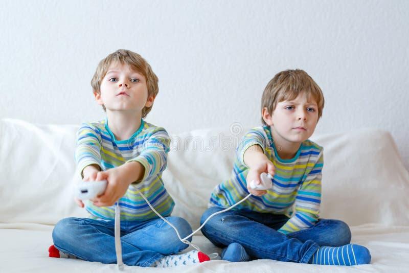Två pojkar för liten unge som hemma spelar videospelet royaltyfri fotografi