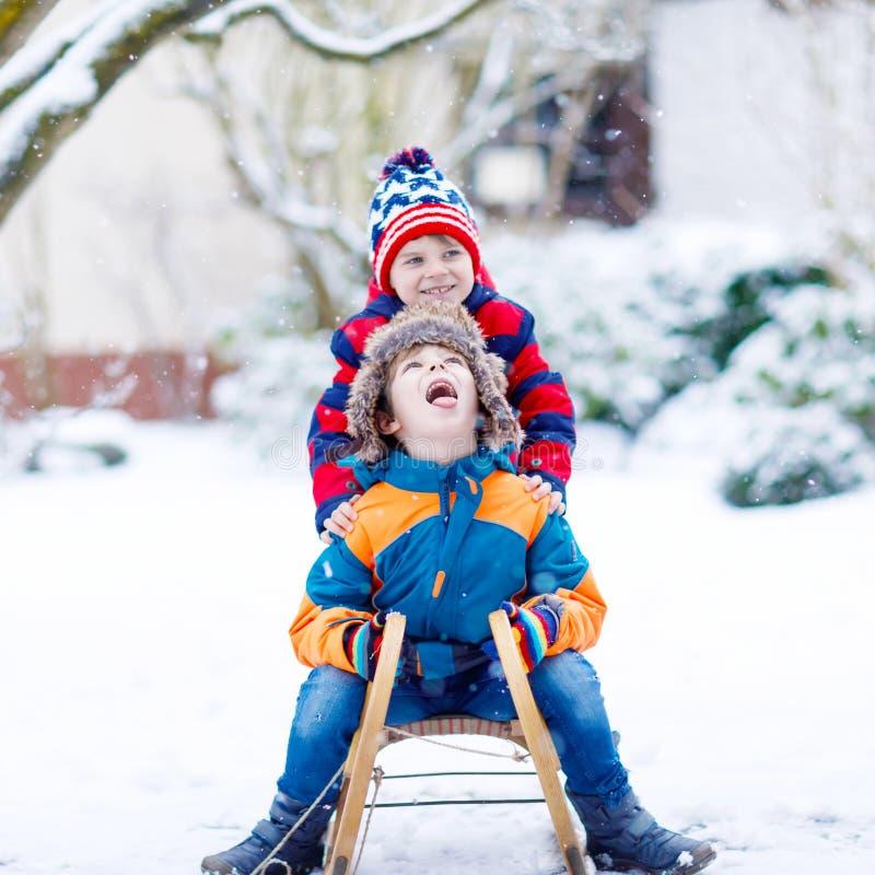 Två pojkar för liten unge som tycker om släden, rider i vinter royaltyfri bild