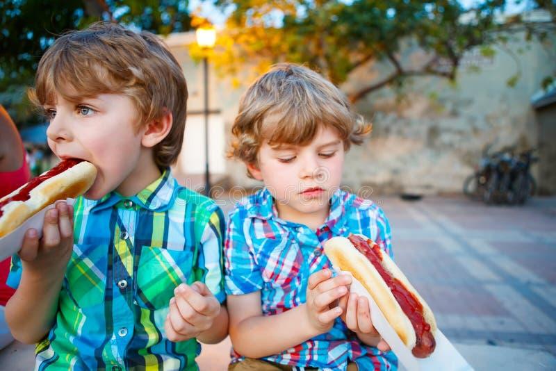 Två pojkar för liten unge som utomhus äter varmkorvar royaltyfria foton