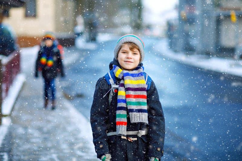 Två pojkar för små ungar av elementär grupp som går till skolan under snöfall Lyckliga barn som har roligt och spelar med arkivbild