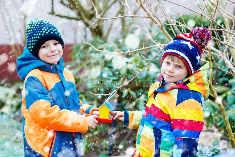 Två pojkar för små ungar som hänger fågelhuset på trädet för matning i vinter royaltyfri bild