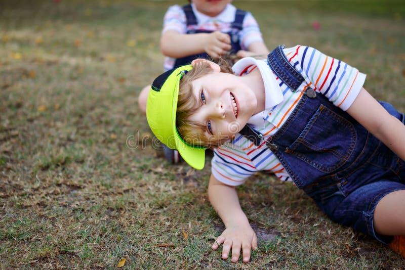 Två pojkar för små ungar som har gyckel i, parkerar, lyckliga bästa vän som spelar, kamratskapbegrepp Syskonbröder, kopplar samma fotografering för bildbyråer