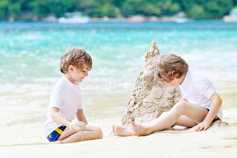 Två pojkar för små ungar som har gyckel med byggande av en sandslott på den fråna Seychellerna tropiska stranden barn som tillsam royaltyfri fotografi