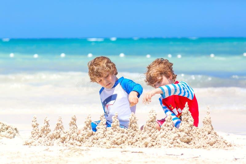 Två pojkar för små ungar som har gyckel med byggande av en sandslott på den tropiska stranden på ön Sunt spela för barn royaltyfri bild