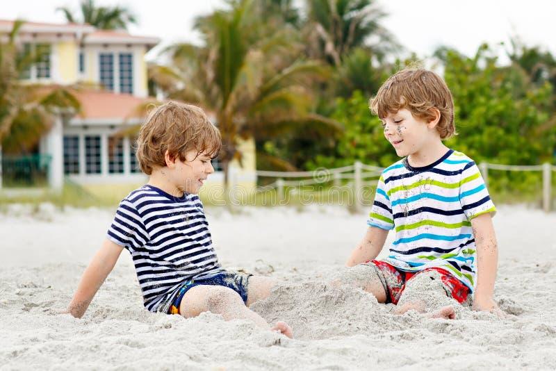 Två pojkar för små ungar som har gyckel med byggnadssandslotten på den tropiska stranden, lyckligt spela för bästa vän syskon arkivbilder