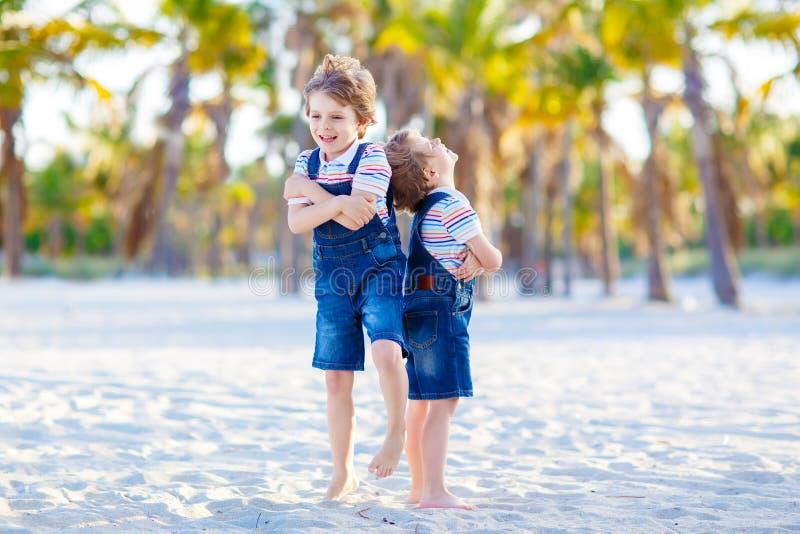 Två pojkar för små ungar som har gyckel på den tropiska stranden arkivbilder