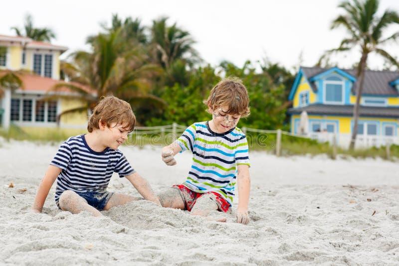 Två pojkar för små ungar som har gyckel på den tropiska stranden, lyckliga bästa vän som spelar, kamratskapbegrepp Syskonbröder royaltyfria foton