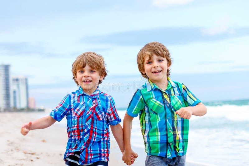 Två pojkar för små ungar som kör på stranden av havet royaltyfri foto