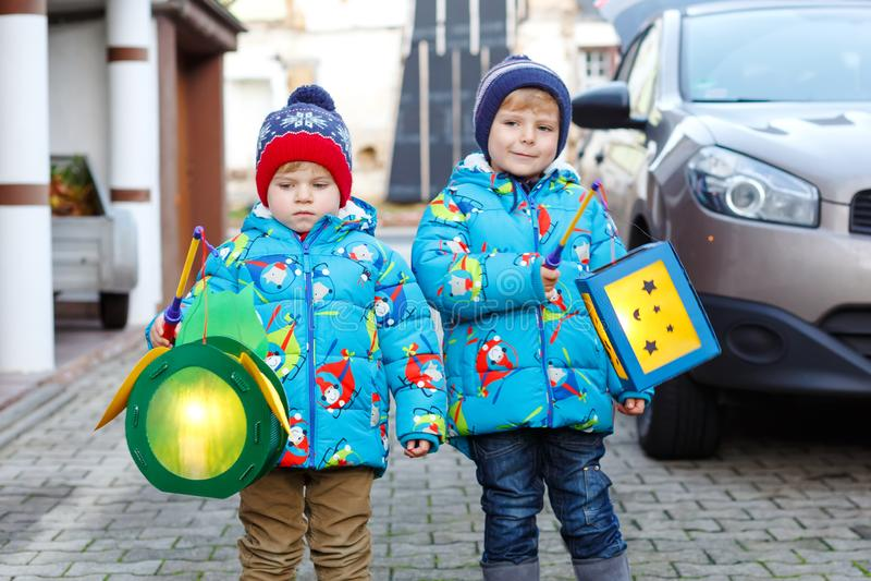 Två pojkar för små ungar som rymmer selfmade lyktor för en allhelgonaafton- eller St Martin procession Härliga bröder som är gull royaltyfri fotografi