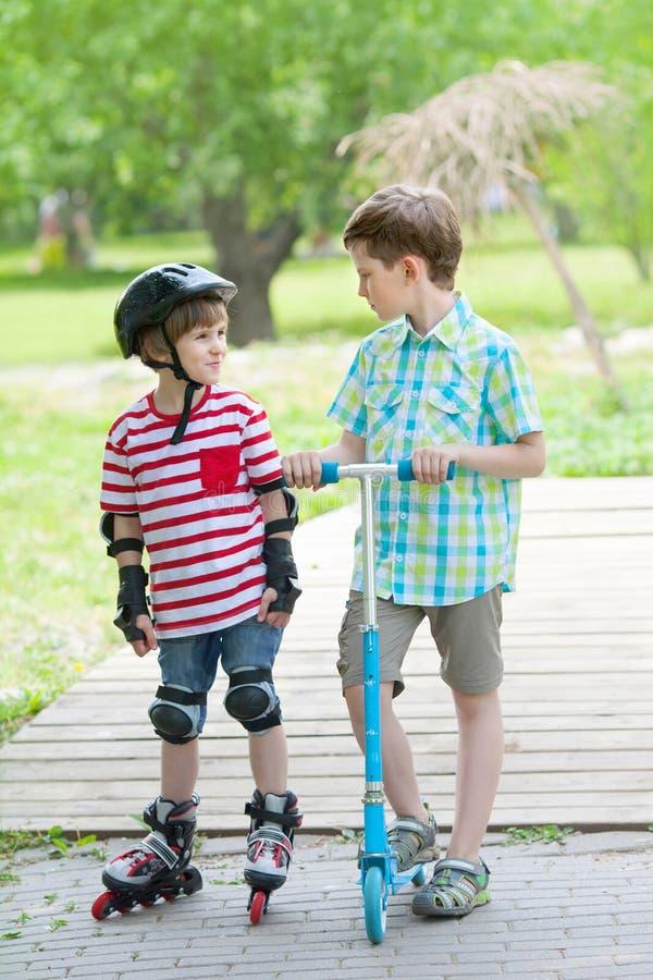 Två pojkar går i stad parkerar royaltyfria foton